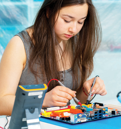 Girl working on circuit board.