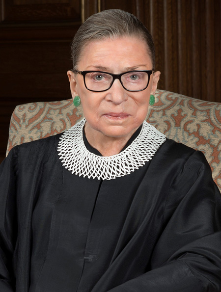Ruth Bader Ginsburg sitting in chair wearing judge's robe.