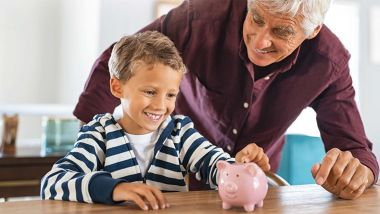 Adult and boy smiling putting a coin in a piggy bank.