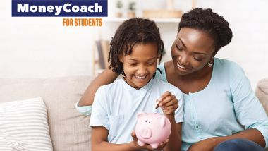 Mother and daughter putting money in a piggy bank.