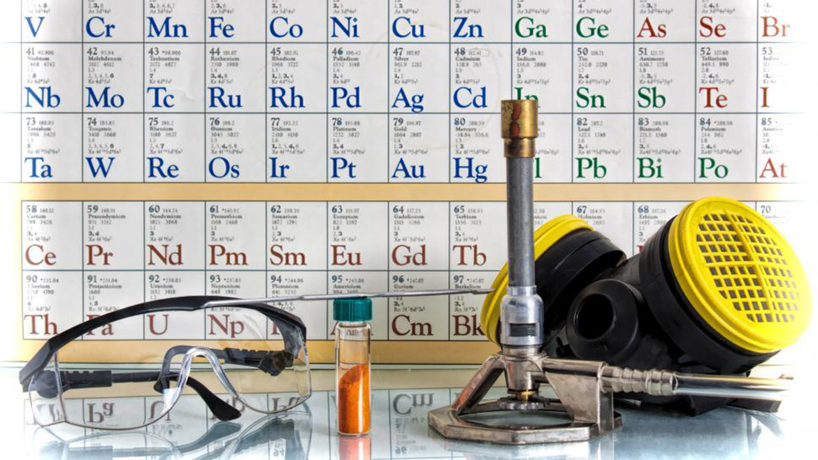 periodic table poster behind scientific tools: bunsen burner, goggles, vial of solution, gas mask.