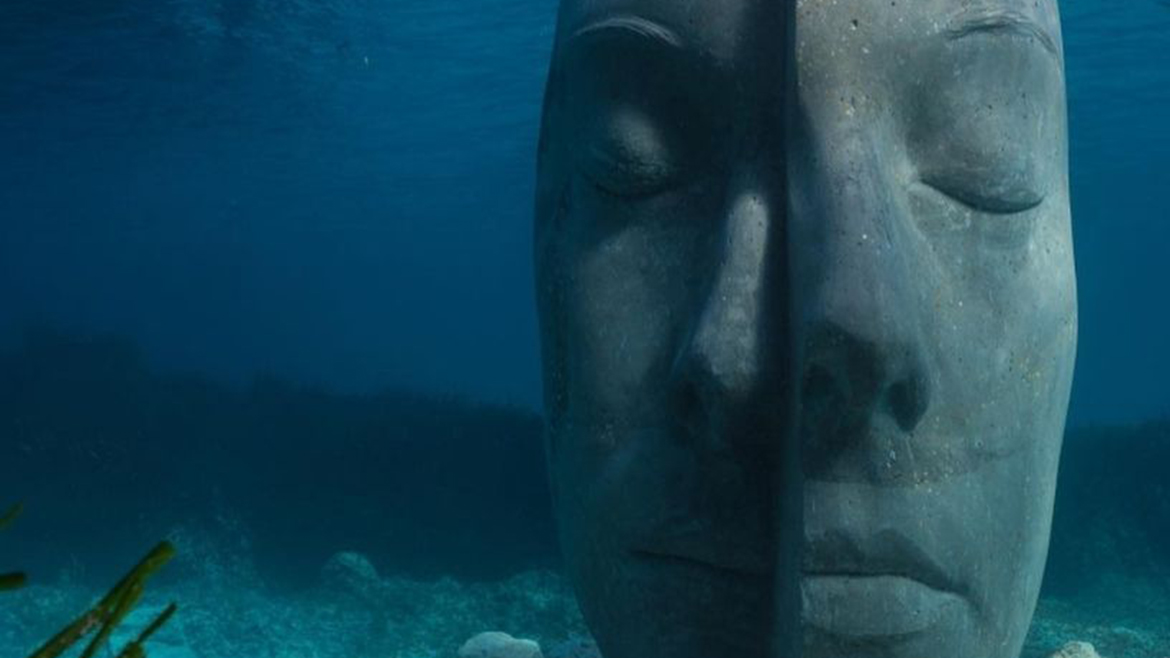 sculpture of a head, eyes closed, underwater.