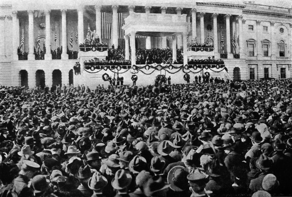 Old black and white photo with crowd in front of White House. Warren G. Harding is standing in front.